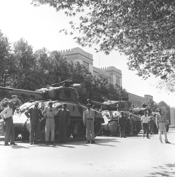 FILE -- In this August 16, 1953 file photo, Iranian army troops and tanks stand in front of Central Police headquarters after the attempted coup d'etat against Iranian Premier Mohammad Mossadeq in Tehran, Iran. On Tuesday, Aug. 27, 2013, Iran's parliament approved fast tracking debate on a bill that seeks to sue the U.S. for its involvement in the 1953 coup that overthrew the country's democratically elected prime minister. Newly declassified documents revealed recently offer more details of how the CIA orchestrated the overthrow of Iranian Prime Minister Mohammed Mossadegh 60 years ago. (AP Photo, File)
