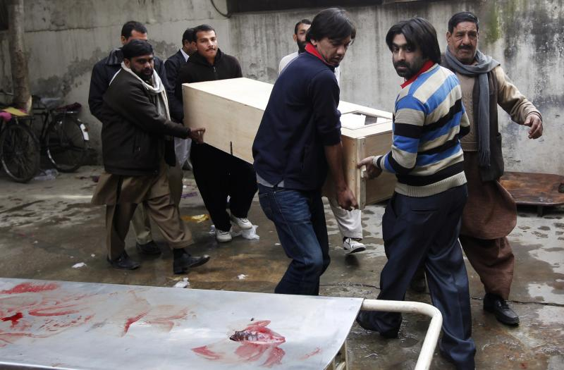 Relatives carry the casket of a victim who was killed in a bomb attack, at a hospital morgue in Rawalpindi