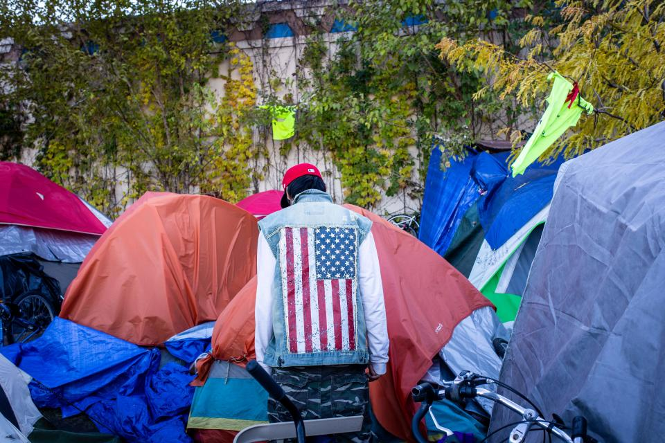 TOPSHOT - More than 200 people live at the large encampment along Hiawatha and Cedar Avenues in Minneapolis, Minnesota on October 22, 2018. - At the tent city for homeless people, the path is strewn with used syringes. Some are shooting up in the open. Dozens have been found unconscious. At least two have died. Most of the more than 200 people here are Native Americans, who have spontaneously gathered over the past few months in this otherwise economically prosperous city. The existence of the camp against a backdrop of gleaming skyscrapers is shining a light on a homelessness crisis sparked by a lack of affordable housing, mental health care and drug addiction treatment. Native Americans are disproportionately affected in all cases. (Photo by Kerem Yucel / AFP)        (Photo credit should read KEREM YUCEL/AFP via Getty Images)