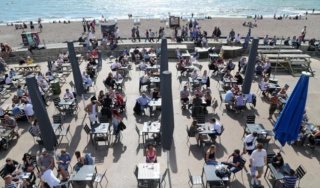 Customers enjoy the sunshine in a bar on the promenade in Brighton