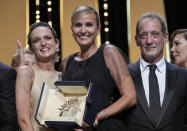 Director Julia Ducournau, center, winner of the Palme d'Or for the film 'Titane' poses with Agathe Roussell, left, and Vincent Lindon during the awards ceremony at the 74th international film festival, Cannes, southern France, Saturday, July 17, 2021. (AP Photo/Vadim Ghirda)