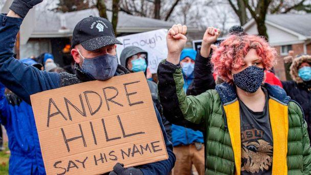 PHOTO: Protesters raise their fists and observe a moment of silence during a demonstration against the police killing of Andre Hill in the neighborhood where he was shot, in Columbus, Ohio, on Dec. 24, 2020. (Stephen Zenner/AFP via Getty Images)