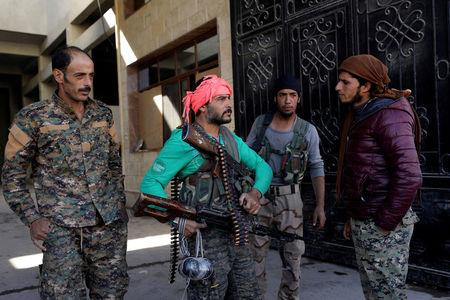 FILE PHOTO: Fighters from the Syrian Democratic Forces (SDF) stand together in Raqqa