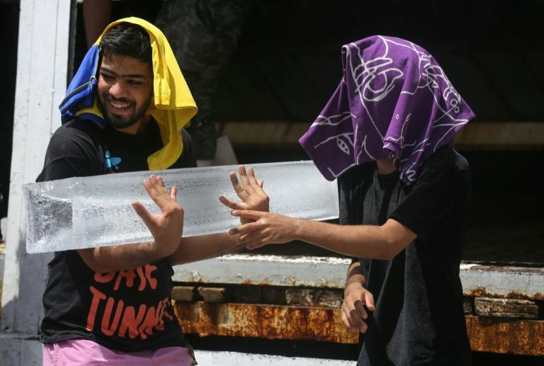Iraqi youths buy ice blocks at a factory in the Baghdad district of Sadr City