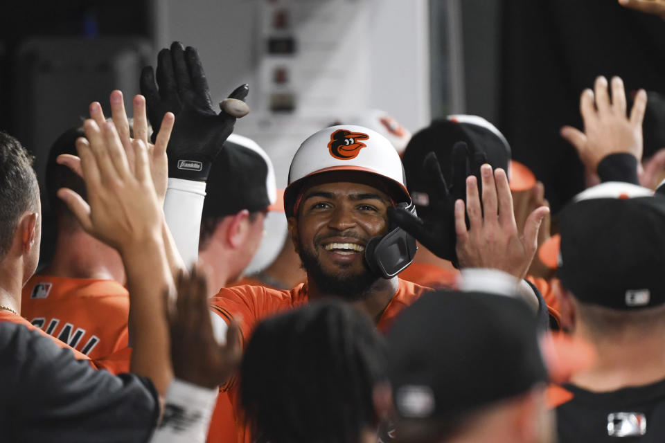 Baltimore Orioles' Kelvin Gutierrez is greeted by teammates in the dugout after hitting a two-run home run against Texas Rangers starting pitcher Jordan Lyles during the seventh inning of a baseball game, Saturday, Sept. 25, 2021, in Baltimore. (AP Photo/Terrance Williams)