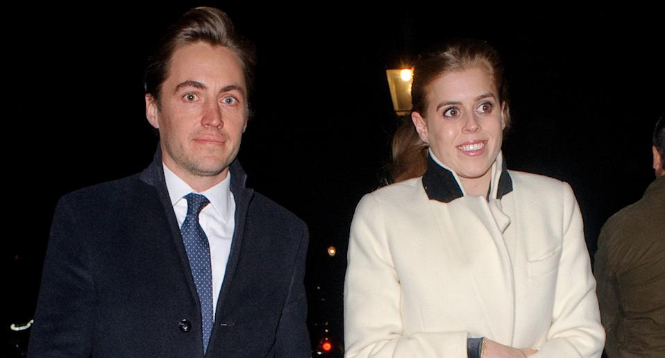 Princess Beatrice dressed in a white coat with a black collar walking at night with her fiance Edoardo Mapello Mozzi