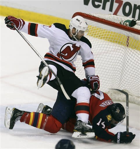 New Jersey Devils' Andy Greene (6) and Florida Panthers' Tomas Fleischmann (14) collide during the second period of Game 5 in a first-round NHL Stanley Cup playoff hockey series in Sunrise, Fla., Saturday, April 21, 2012. (AP Photo/J Pat Carter)