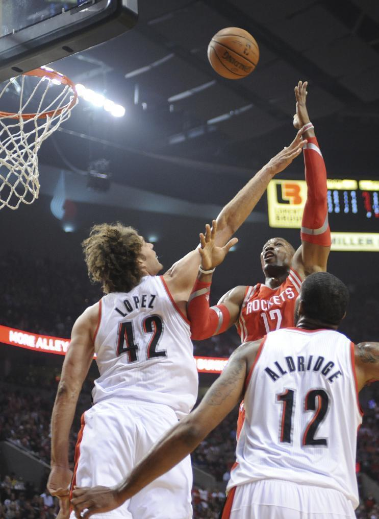 Houston Rockets' Dwight Howard (12) shoots against Portland Trail Blazers' Robin Lopez (42) and LaMarcus Aldridge (12) during the first half of game six of an NBA basketball first-round playoff series game in Portland, Ore., Friday May 2, 2014. (AP Photo/Greg Wahl-Stephens)