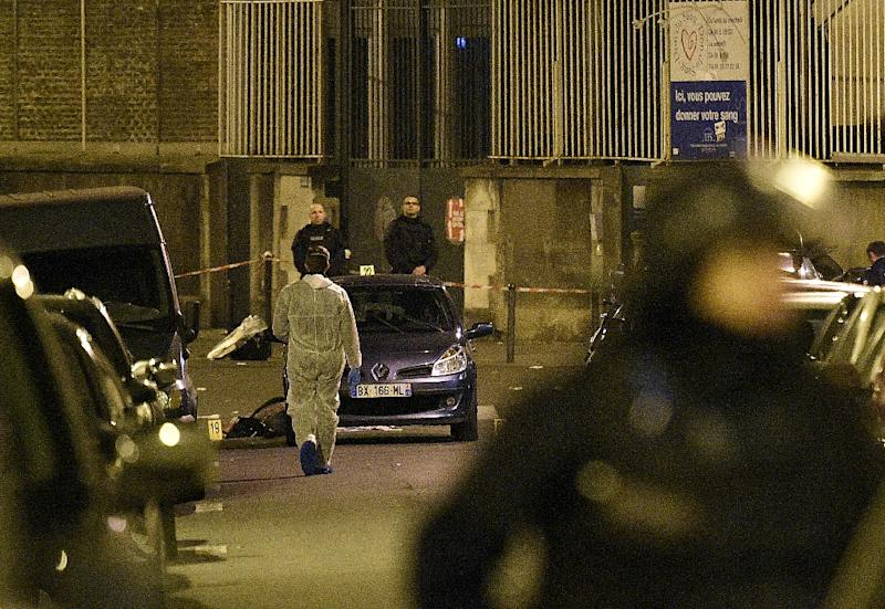 A forensic expert (Rear L in white) and special police work at the attack scene rue Bichat, in central Paris on November 14, 2015
