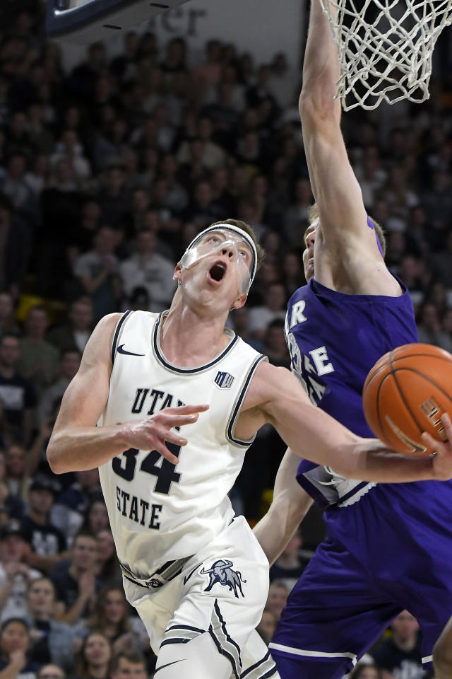 Utah State forward Justin Bean (34) shoots as Weber State forward Tim Fuller defends during the first half of an NCAA college basketball game Friday, Nov. 8, 2019, in Logan, Utah. (AP Photo/Eli Lucero)