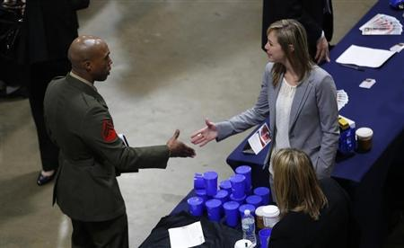 A U.S. Marine (L) shakes hands at an employers booth at the Hiring Our Heroes job fair in Washington January 10, 2014. REUTERS/Kevin Lamarque