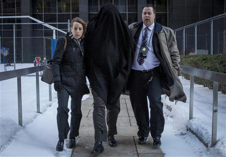 A hooded suspect is escorted by FBI agents from their Manhattan offices in New York February 11, 2014. REUTERS/Brendan McDermid