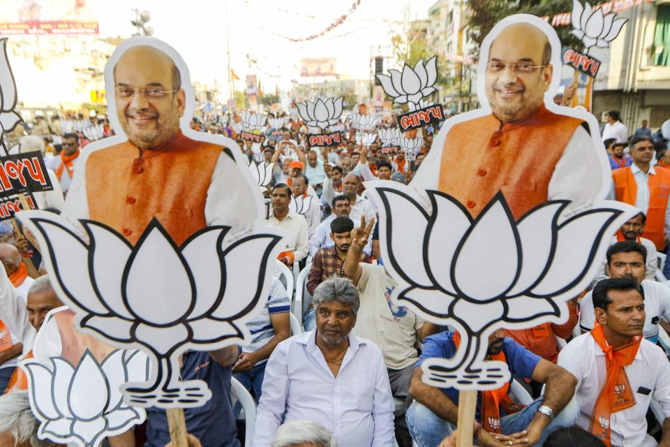 BJP supporters hold cutouts of party president Amit Shah with the party symbol during a public rally in Ahmadabad on 26 March.