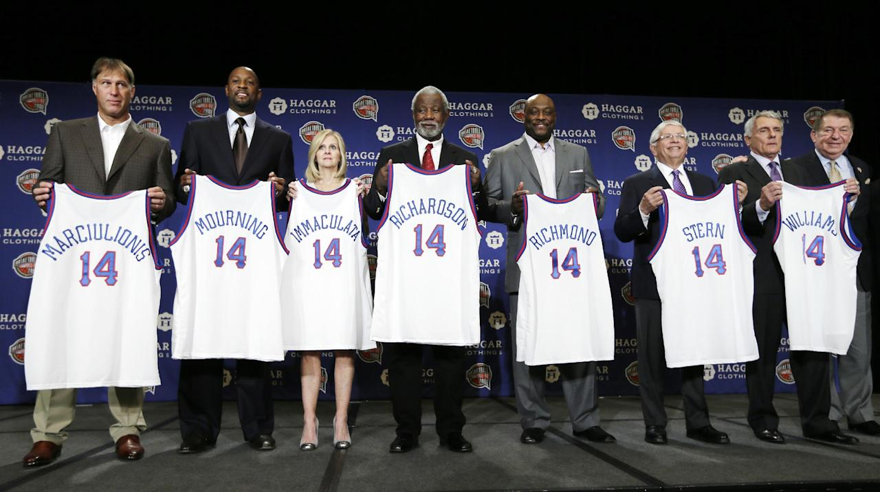 Sarunas Marciulionis, from left, Alonzo Mourning, Judy Martelli, Nolan Richardson, Mitch Richmond, David Stern and Gary Williams pose for a photo on stage with their jerseys and Jerry Colangelo, right, chairman of the Naismith Memorial Basketball Hall of Fame, during the Naismith Memorial Basketball Hall of Fame class of 2014 announcement, Monday, April 7, 2014, in Dallas. (AP Photo/Charlie Neibergall)