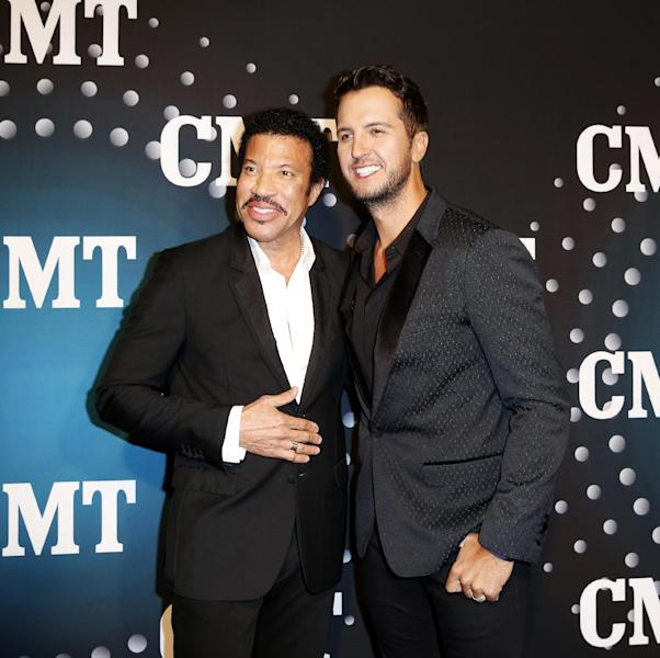 """Lionel Richie and Luke Bryan pose on the red carpet at the CMT """"Artists of the Year"""" event at Bridgestone Arena, on Tuesday, December 3, 2013, in Nashville, Tenn. (Photo by Donn Jones/Invision/AP)"""