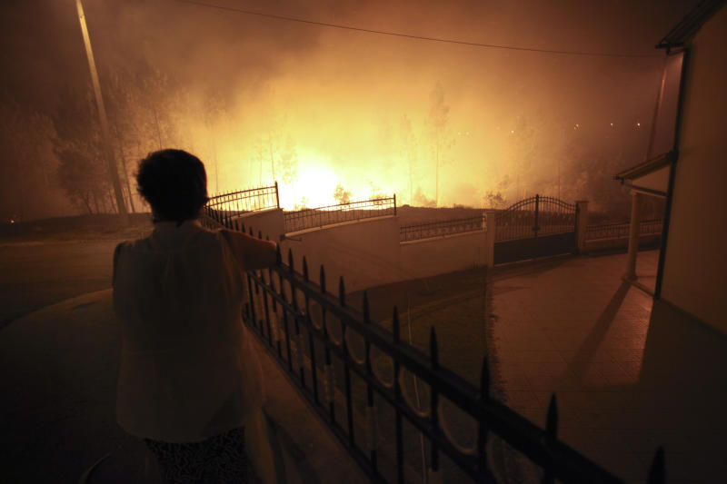 A woman watches the fire approaching a house in Ribeira do Farrio, near Ourem, Portugal, Monday, Sept. 3, 2012. A Portuguese official says authorities have asked other European countries to send help as the country's firefighters struggle to contain forest blazes being fueled by high temperatures and strong winds. (AP Photo/Francisco Seco)