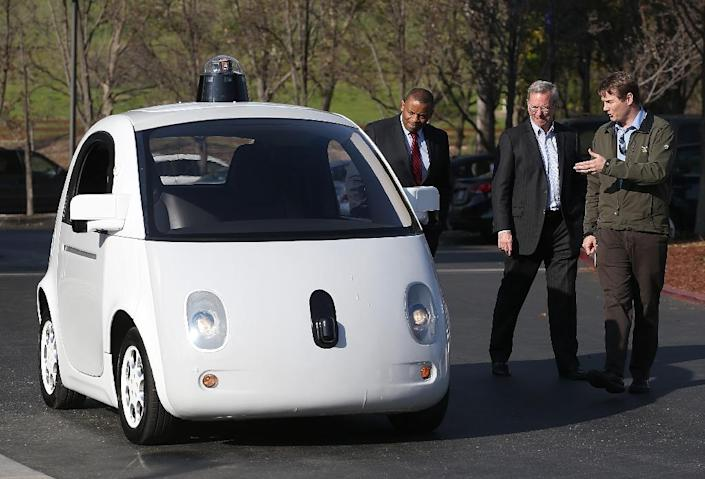 Google's Chris Urmson (R) shows a Google self-driving car to US Transportation Secretary Anthony Foxx (L) and Google Chairman Eric Schmidt (C) at the Google headquarters on February 2, 2015 in Mountain View, California (AFP Photo/Justin Sullivan)