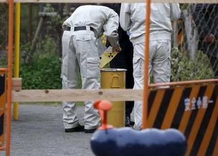 A worker of Tokyo's Toshima ward office puts a sticker on a container holding a fragment of an unknown object after it was dug up from the ground near playground equipment at a park in Toshima ward, Tokyo April 24, 2015. REUTERS/Toru Hanai