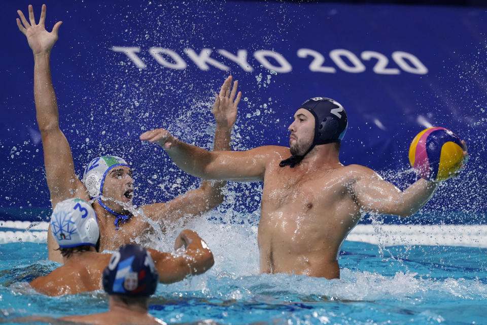 Serbia's Dusan Mandic (2) shoots against Italy's Stefano Luongo (3) and Vincenzo Dolce (12) during a quarterfinal round men's water polo match at the 2020 Summer Olympics, Wednesday, Aug. 4, 2021, in Tokyo, Japan. (AP Photo/Mark Humphrey)