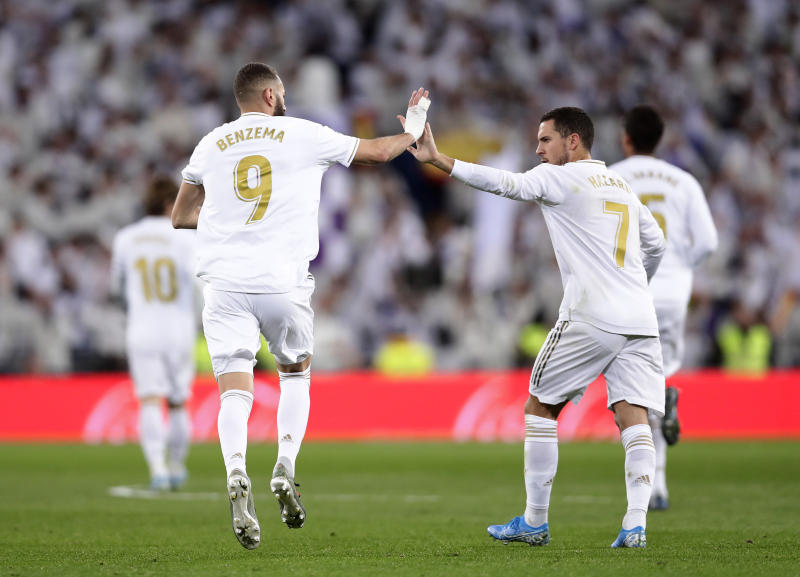 Real Madrid's Eden Hazard congratulates Real Madrid's Karim Benzema after he scored his side's first goal during the Spanish La Liga soccer match between Real Madrid and Real Sociedad at the Bernabeu stadium in Madrid, Spain, Spain, Saturday, Nov. 23, 2019. (AP Photo/Manu Fernandez)