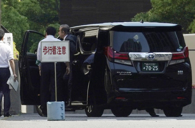 Former Nissan chairman Carlos Ghosn, right, gets off a car as he arrives at Tokyo District Court for a pre-trial meeting Thursday, May 23, 2019, in Tokyo. Ghosn, who is out on bail, has been charged with under-reporting his post-retirement compensation and breach of trust in diverting Nissan money and allegedly having it shoulder his personal investment losses. (AP Photo/Eugene Hoshiko)