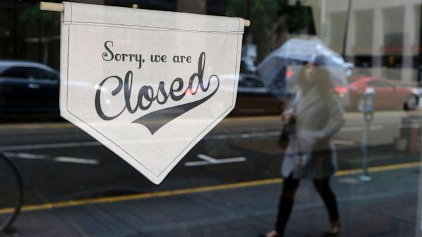 PHOTO: A woman walks along through the Financial District past the closed Homage Ltd. restaurant which is normally open for breakfast and lunch, March 16, 2020, in San Francisco. (Eric Risberg/AP, FILE)