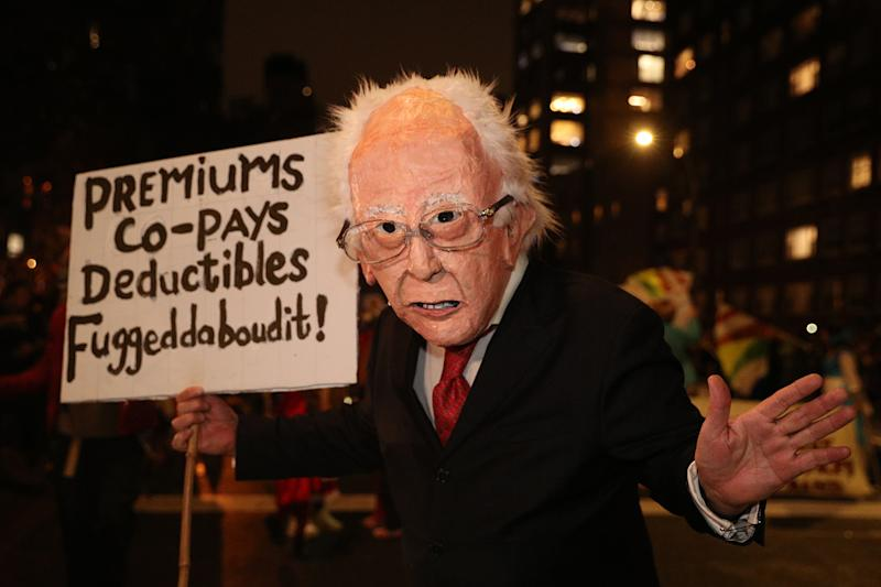 A man dressed as Bernie Sanders carrying a sign marches in the 46th annual Village Halloween Parade in New York City. (Gordon Donovan/Yahoo News)