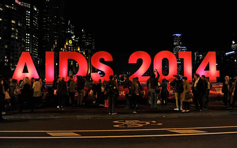 People gather next to a sign reading AIDS 2014 in Melbourne on July 18, 2014 ahead of the 20th International AIDS Conference beginning this weekend (AFP Photo/)