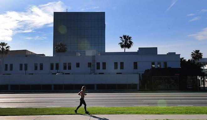 A woman on her morning jog runs along a deserted Santa Monica Boulevard in Beverly Hills, California. The state has told its 40 million residents to stay at home, the most drastic move yet in the US. Photo: AFP