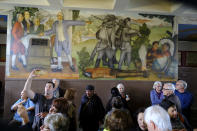 """FILE - In this Aug. 1, 2019, file photo, people fill the main entryway of George Washington High School to view the controversial 13-panel, 1,600-square foot mural, the """"Life of Washington,"""" during an open house for the public in San Francisco. The San Francisco school board has voted to remove the names of George Washington and Abraham Lincoln from public schools after officials deemed them and other prominent figures, including Sen. Dianne Feinstein unworthy of the honor. After months of controversy, the board voted 6-1 Tuesday, Jan. 26, 2021, in favor of renaming 44 San Francisco school sites with new names with no connection to slavery, oppression, racism or similar criteria, the San Francisco Chronicle reported. (AP Photo/Eric Risberg, File)"""