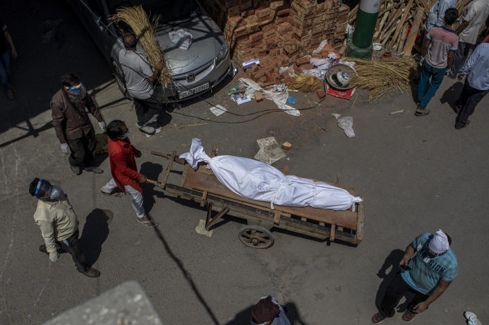 A man transports a dead body on a handcart to a ground that has been converted into a crematorium for mass cremation of COVID-19 victims, in New Delhi, India, Saturday, April 24, 2021. Delhi has been cremating so many bodies of coronavirus victims that authorities are getting requests to start cutting down trees in city parks, as a second record surge has brought India's tattered healthcare system to its knees. (AP Photo/Altaf Qadri)