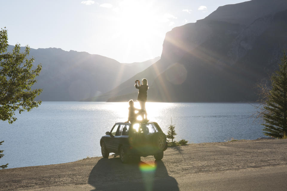 Woman takes pic from car roof while man relaxes