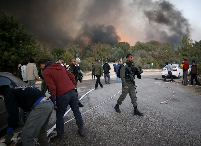 Israeli security forces and volunteers help firefighters battle to control a fire that broke out in the Israeli town of Nataf, west of the Arab Israeli town of Abu Ghosh, along the border with the occupied West Bank on November 25, 2016 (AFP Photo/Ahmad Gharabli)