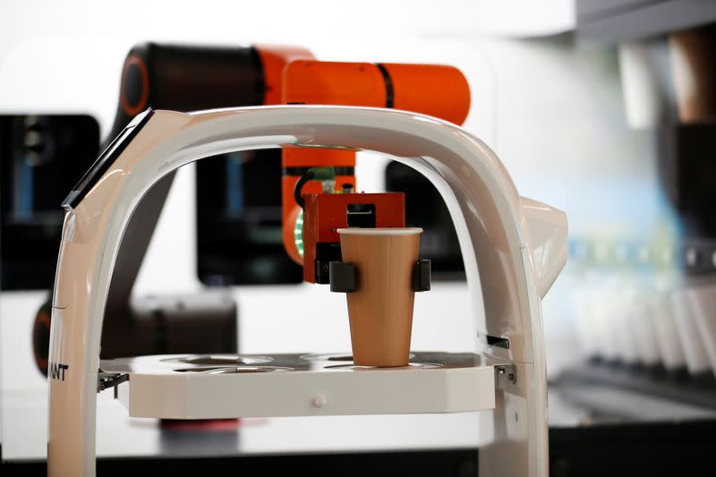 A robot that takes orders, makes coffee and brings the drinks straight to customers at their seats is seen at a cafe in Daejeon