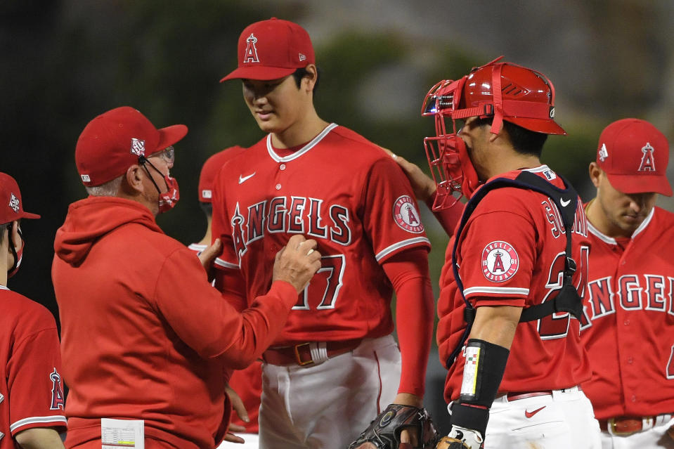 Los Angeles Angels starting pitcher Shohei Ohtani, center, is taken out of the game by manager Joe Maddon, left, as catcher Kurt Suzuki pats him on the back during the sixth inning of a baseball game against the Tampa Bay Rays Wednesday, May 5, 2021, in Anaheim, Calif. (AP Photo/Mark J. Terrill)