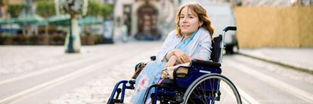 Disabled woman in wheelchair outdoors in plaza.
