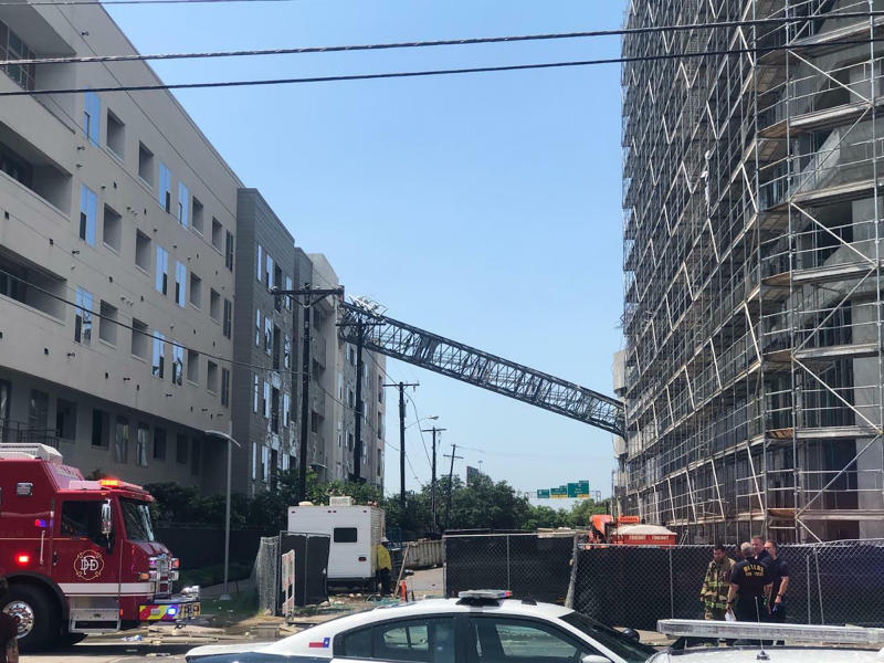 Officials respond to the scene after a crane collapsed into Elan City Lights apartments in Dallas amid severe thunderstorms Sunday, June 9, 2019. (Michael Santana via AP)