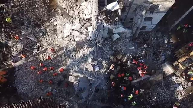 In this aerial view taken from a video by AFPTV, emergency workers clear debris at a damaged building in Thumane, 34 kilometres (about 20 miles) northwest of capital Tirana (ELIS KRUJA/AFP via Getty Images)