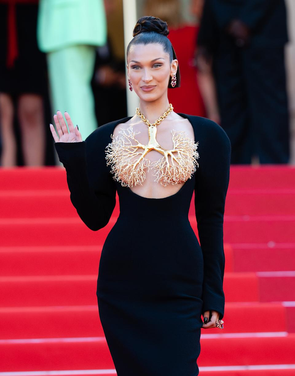 Bella Hadid wears a black dress and lung-shaped gold necklace at the