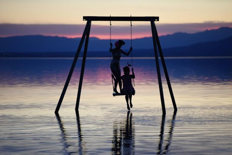 Attendees play on a swing installed in the Salton Sea on the first day of the Bombay Beach Biennale