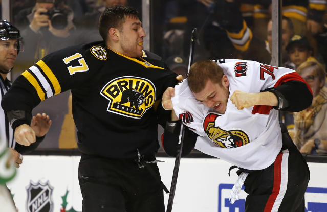 Boston Bruins' Milan Lucic (17) fights with Ottawa Senators' Mark Borowiecki during the second period of an NHL hockey game in Boston Saturday, Dec. 13, 2014. (AP Photo/Winslow Townson)