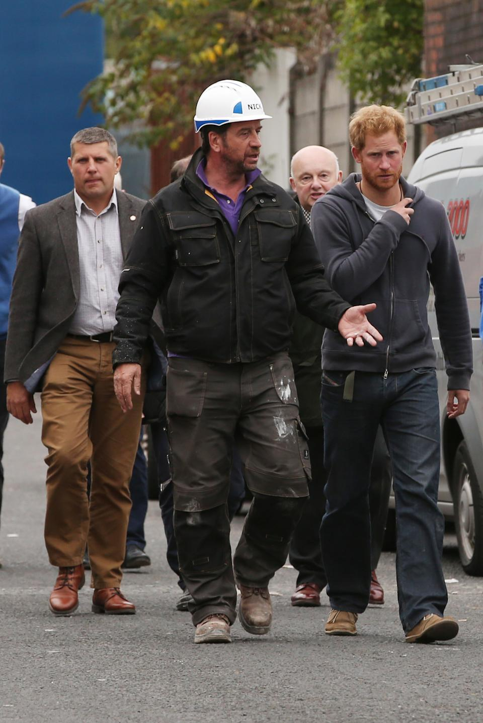 Prince Harry leaves with the show's host Nick Knowles after a visit to the BBC's DIY SOS Team for The Big Build: Veteran's Special at a street in Manchester.