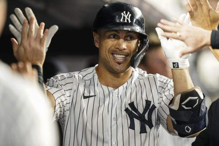 New York Yankees' Giancarlo Stanton celebrates with teammates after hitting a home run during the third inning of a baseball game against the Texas Rangers Tuesday, Sept. 21, 2021, in New York. (AP Photo/Frank Franklin II)