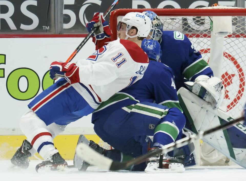 Montreal Canadiens right wing Brendan Gallagher (11) falls next to Vancouver Canucks goaltender Thatcher Demko (35) and defenseman Olli Juolevi (48) during the second period of an NHL hockey game Thursday, Jan. 21, 2021, in Vancouver, British Columbia. (Jonathan Hayward/The Canadian Press via AP)