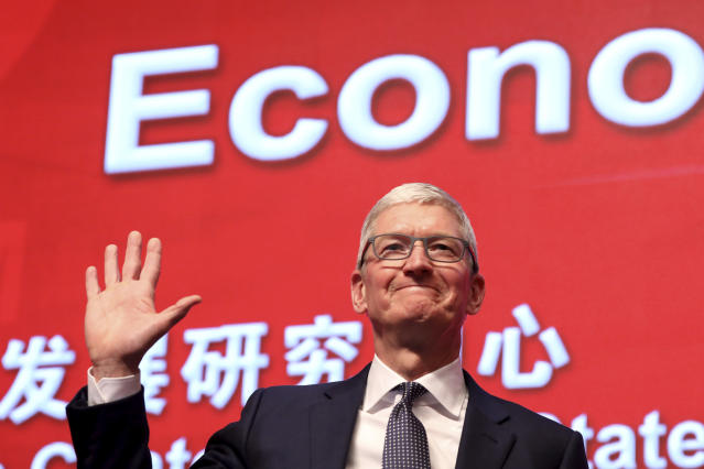 FILE - In this Saturday, March 23, 2019, file photo, Apple CEO Tim Cook waves as he arrives for the Economic Summit held for the China Development Forum in Beijing, China. Few U.S. companies are more vulnerable to a trade war with China than Apple. The company relies on factories in China to assemble the iPhones that generate most of its profits; it has also cultivated a loyal following in the country. (AP Photo/Ng Han Guan, File)