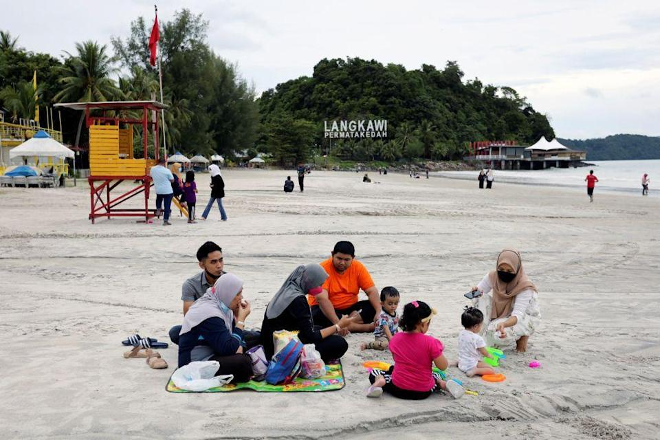 People enjoy a picnic at Cenang Beach as Langkawi gets ready to open to domestic tourists from September 16, 2021. — Reuters pic