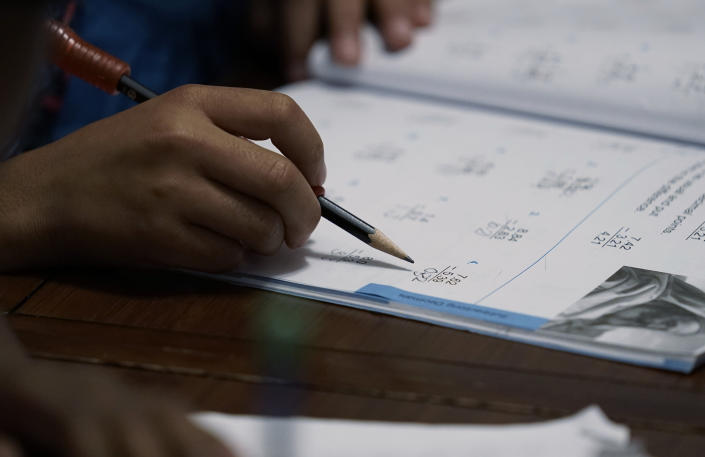 Felicity Brown, 9, uses a workbook to practice math with her parents and siblings at home in Austin, Texas, on Tuesday, July 13, 2021. After homeschooling during the pandemic, the Brown family has switched to homeschooling their kids permanently using a Catholic-based curriculum and won't be sending them back to in-person schools in the fall. (AP Photo/Eric Gay)