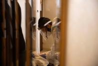 An ultra-Orthodox Jewish volunteer from Chasdei Amram, which provides home relief to people affected by the coronavirus disease (COVID-19), wears personal protective equipment (PPE) as he visits an elderly woman in Jerusalem