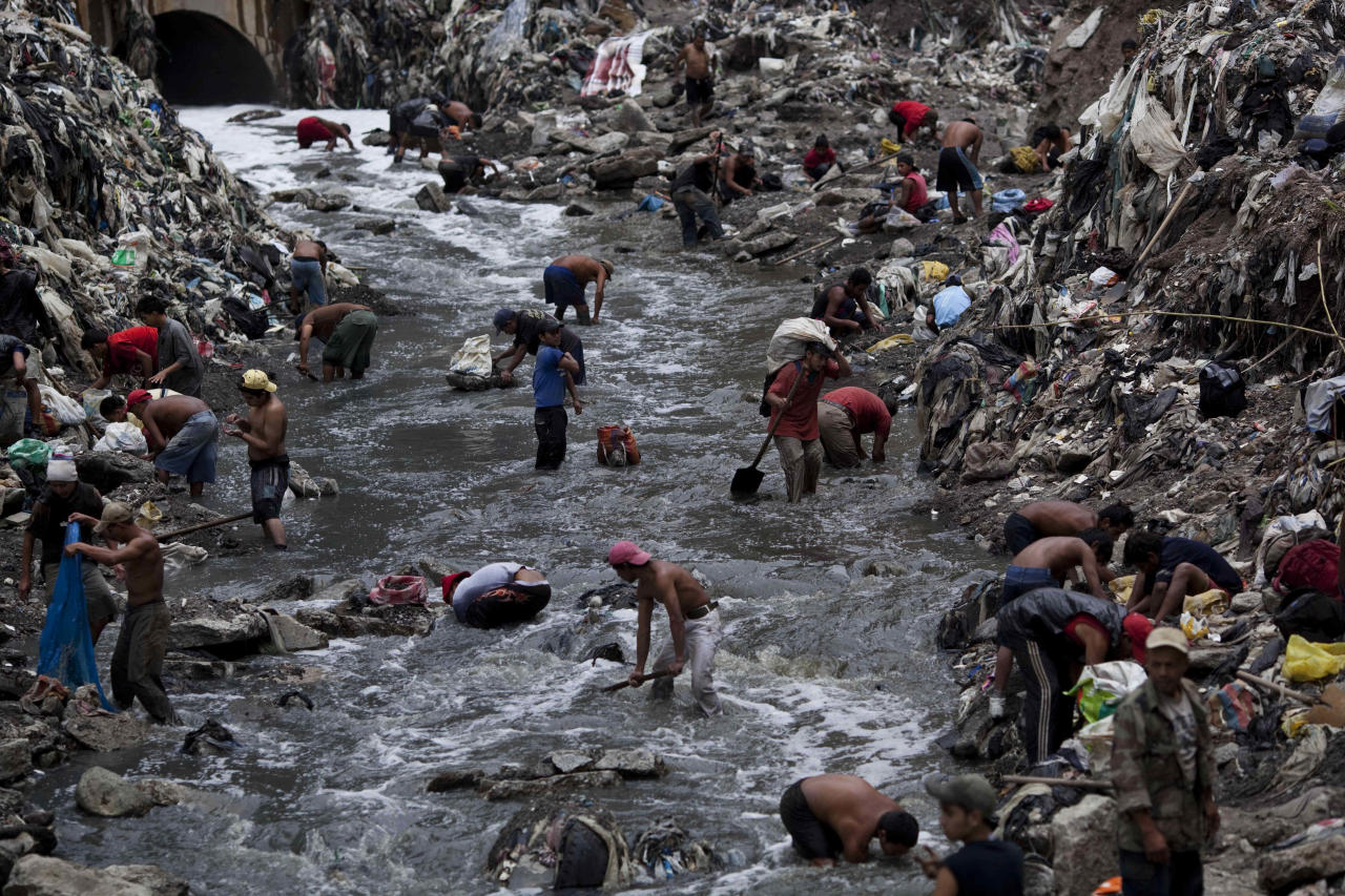 "In this photo taken Wednesday Oct. 19, 2011, people search for scrap metal in contaminated water at the bottom of one of the biggest trash dumps in the city, known as ""The Mine,"" in Guatemala City. Hundreds of informal workers descend daily into the mounds of the landfill and the rushing waters that come from a storm tunnel and a sewer at the bottom of a gorge to search for scrap metal to sell. This activity known locally as ""mining"" is extremely dangerous due to mud slides and collapses, but earns many of them about 150 quetzals ($20 dollars) a day, nearly twice the minimum daily wage. AP Photo/Rodrigo Abd)"