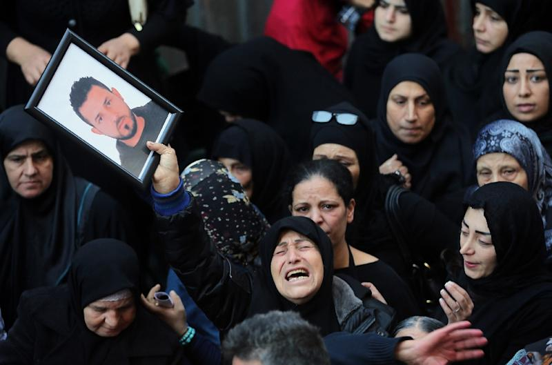 A relative of Samer Huhu, killed in a twin bombing attack that rocked a busy shopping street in the area of Burj al-Barajneh, waves his portrait as she mourns during his funeral in the southern suburb of the capital Beirut on November 13, 2015 (AFP Photo/Joseph Eid)